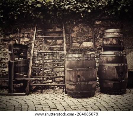 Ancient traditional wine press and oak barrels on Italian street outside restaurant. Traditional old technique of wine-making.  - stock photo