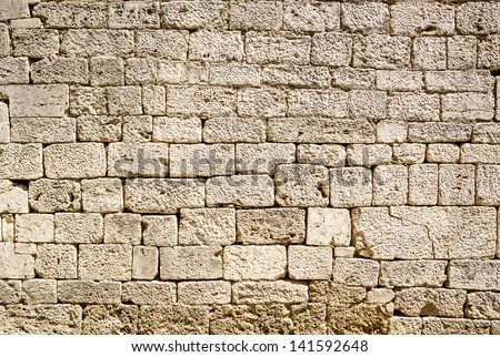 Ancient wall built of white stone - stock photo