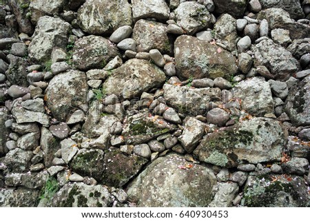 Ancient wall of round and crushed stones with moss