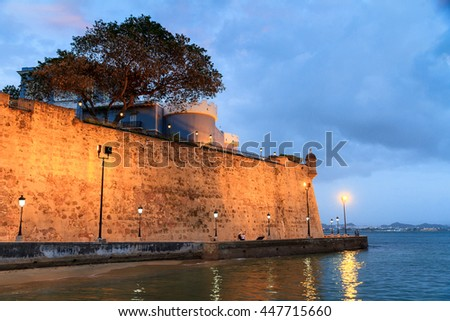 Ancient wall with promenade around the city of San Juan in Puerto Rico at nightfall - stock photo