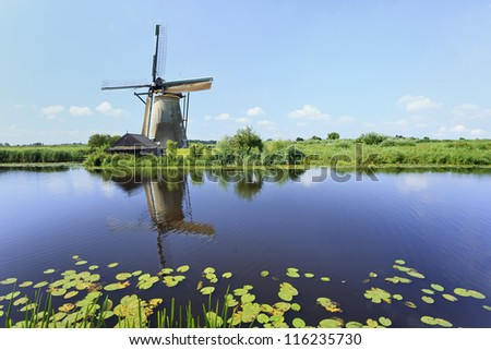Ancient wind mill reflected in a blue canal on a summer day at the famous Kinderdijk, Holland. - stock photo