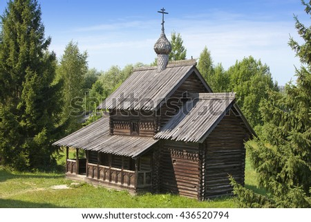 Ancient wooden church on a forest glade. Russia.