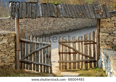 ancient wooden gates against an ancient stone wall