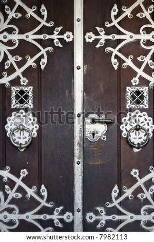 Ancient wooden main entrance with applied metallic decorations