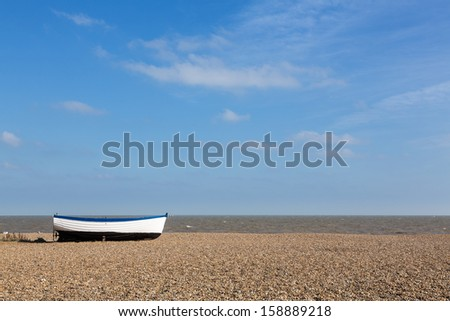 Ancient wooden painted fishing boat on pebble beach by North Sea in Aldeburgh Suffolk on East coast of England - stock photo