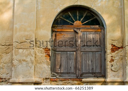 Ancient wooden window with concrete wall in natural rural environment
