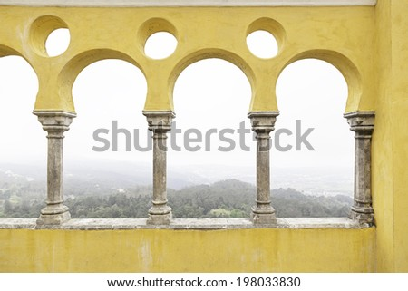 Ancient yellow arches in the Pena Palace, detail of ancient architecture, heritage of humanity, tourism - stock photo