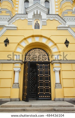 ancient yellow building with larched open door, anterns / yellow middle aged building