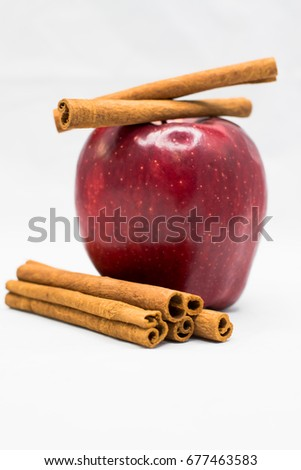And apple and some cinnamon sticks on a white background.