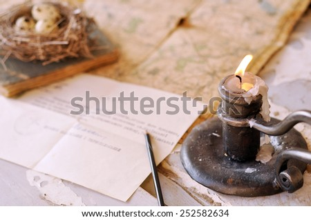 And old map and a forged candlestick - stock photo