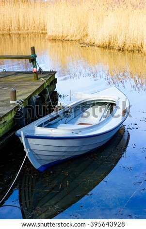 And old traditional hunting canoe moored at the wooden pier in early spring. Windless day with calm water and yellow reed in background. - stock photo