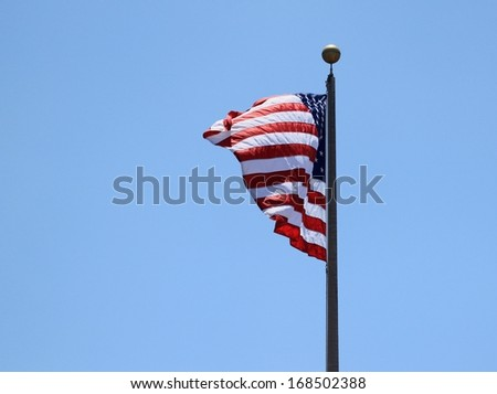 And old USA flag with a blue sky in the background. - stock photo
