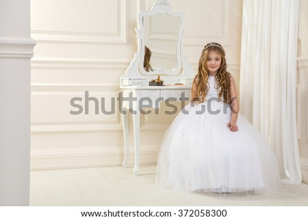 and tiara on his head, sitting in elegant palatial room with a dressing table with mirror in the background - stock photo
