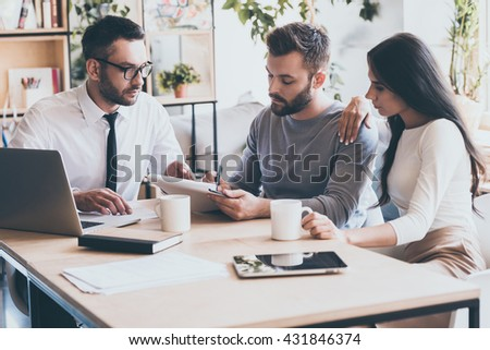 And your signature here. Confident young man signing some document while sitting together with his wife and man in shirt and tie  - stock photo