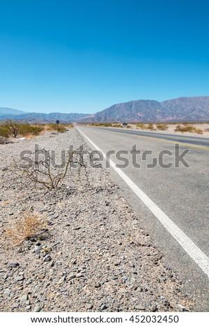 Andean road crossing a barren landscape at high altitude, Salta, Argentina - stock photo