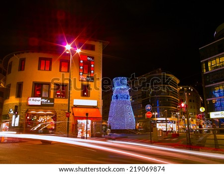 ANDORRA-LA-VELLA, ANDORRA - JANUARY 21: The city centre of Andorra-la-Vella, Andorra on January 21, 2009. Traces from the headlights in the night street and alight snowman on the background.
