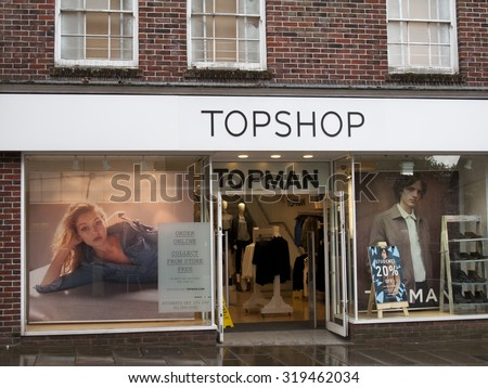 Andover, High Street, Hampshire, England - September 21, 2015: Topshop and Topman fashion store late rain soaked afternoon - stock photo