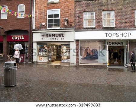 Andover, High Street, Hampshire, England - September 21, 2015: Topshop and Topman fashion store, H Samuel Jewellers and Costa Coffee, late rain soaked afternoon