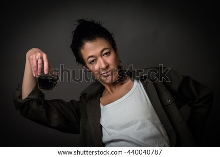 Androgen. Androgynous character drinking from glass on a gray background. Man or woman. Military style.