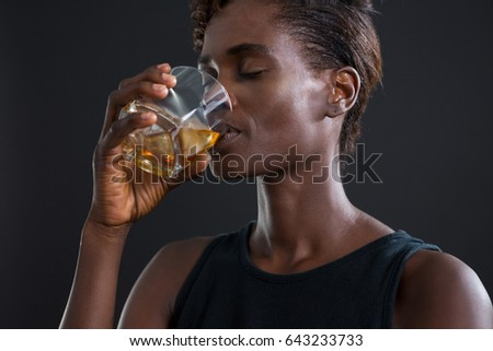 Androgynous man drinking whiskey from glass against grey background