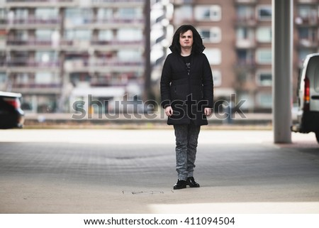 Androgynous man standing on parking lot