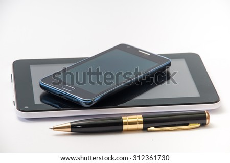Android tablet, mobile phone and black pen. - stock photo