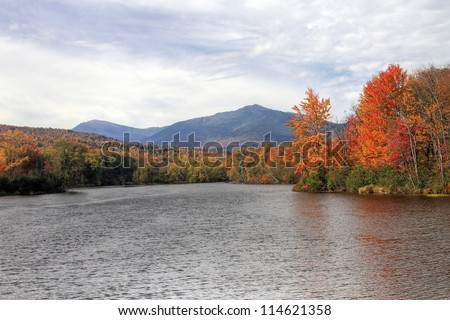 Androscoggin river flowing in Autumn with the White Mountains in background. - stock photo