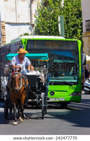 ANDUJAR,SPAIN - September, 6: Participants in the fair of the horse walk on their carriages Andalusian style and typical costume on September, 6, 2014 in Andujar, Spain - stock photo