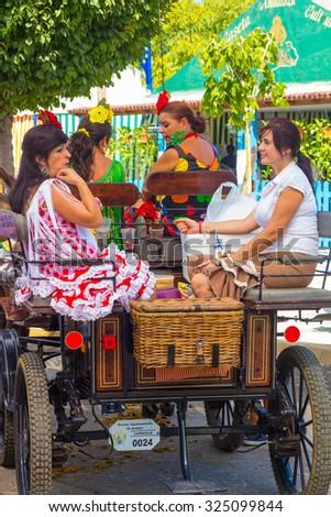 ANDUJAR,SPAIN - September, 6: Women typical Sevillian flamenca suits, walking in the car in the Horse Fair on September, 6, 2014 in Andujar, Spain - stock photo
