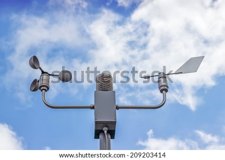 Anemometer and wind vane on blue sky. Measuring wind speed and direction.  The rotating cup anemometer is commonly used to measure wind speed. - stock photo