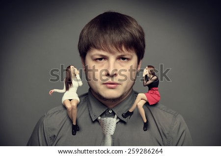 angel and demon sitting in man's shoulders  - stock photo