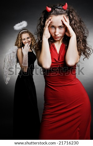 angel and devil over dark background - stock photo