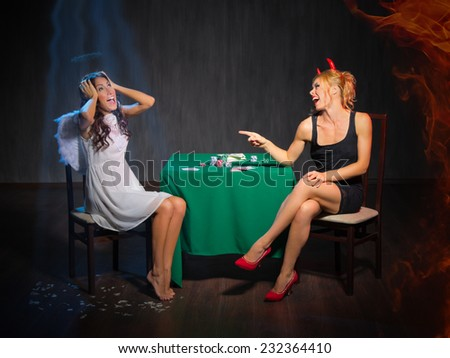 Angel and devil playing cards at room - stock photo