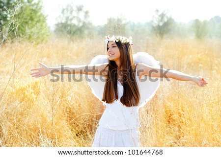 Angel ethnic woman in golden field with feather white wings and flowers crown - stock photo