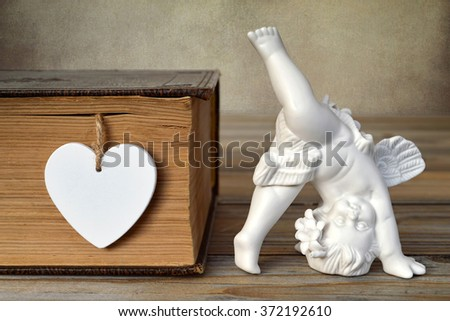 Angel figurine and heart - stock photo