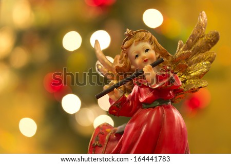 Angel figurine with flute over bokeh background on Christmas