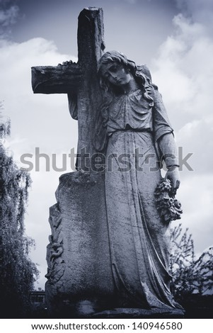 Angel leaning on cross - stock photo