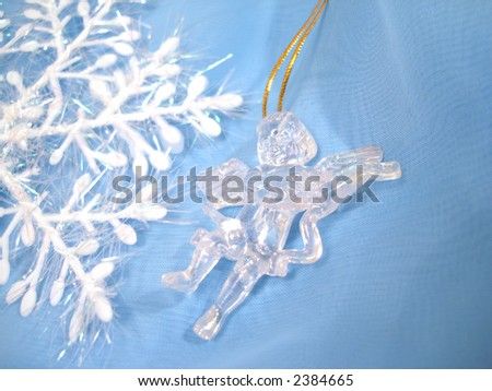 Angel sculpture and snowflake on blue background - stock photo