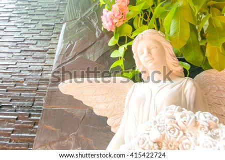 Angel statue in garden. - stock photo