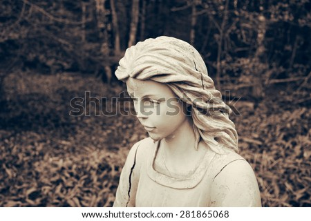 Angel statue portrait in wooded setting. Toned grunge look. - stock photo