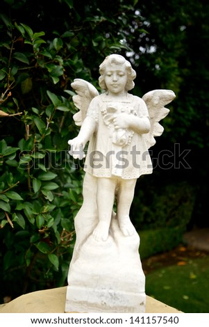 Angel statue stands on a wall near a garden in the San Fernando mission. - stock photo
