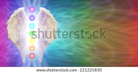 Angel Wings on rainbow colored banner background with seven chakras positioned between wings - stock photo