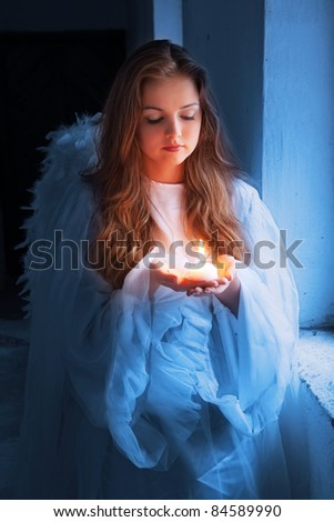 angel with a candle standing near the window. - stock photo