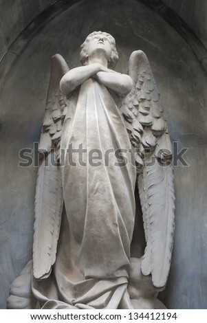 angel with arms crossed and head up - stock photo