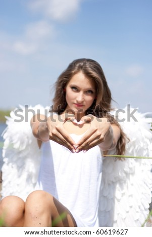 Angel with heart outdoors