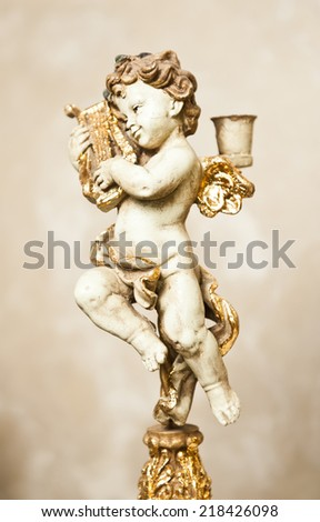 Angel with lyre ornament. Golden ornament. Vintage angel. Ceramic angel playing harp. Cupid as candle holder on marble support, - stock photo