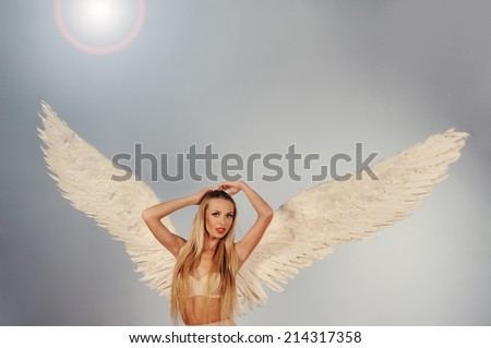 angel with white wings in blue sky - stock photo