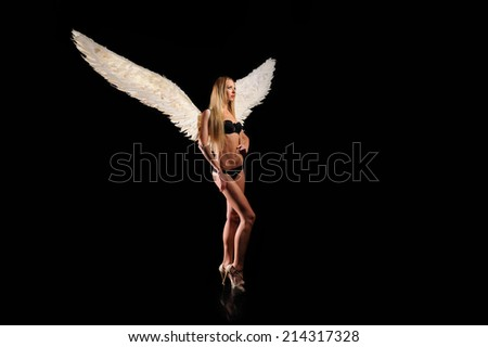 angel with white wings on black background  - stock photo