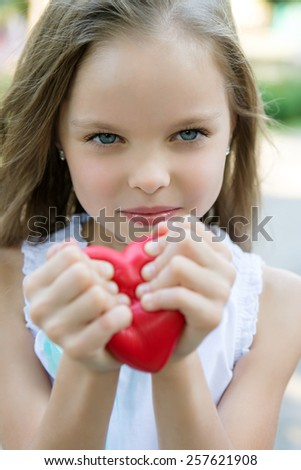 anger little girl  holding a red heart concept of heartbreak outdoor - stock photo