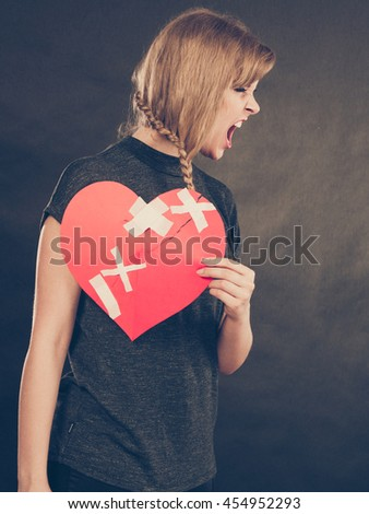 Anger of broken feeling. Furious blonde woman shouting. Angry girl holding repared heart love symbol sign on dark background.